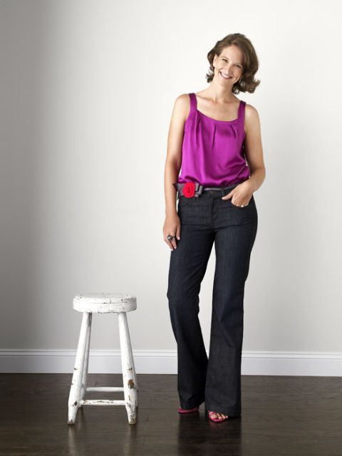 woman in jeans and dark pink top standing by stool