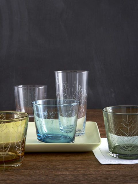 multicolored glassware that has been etched with leafy designs on table