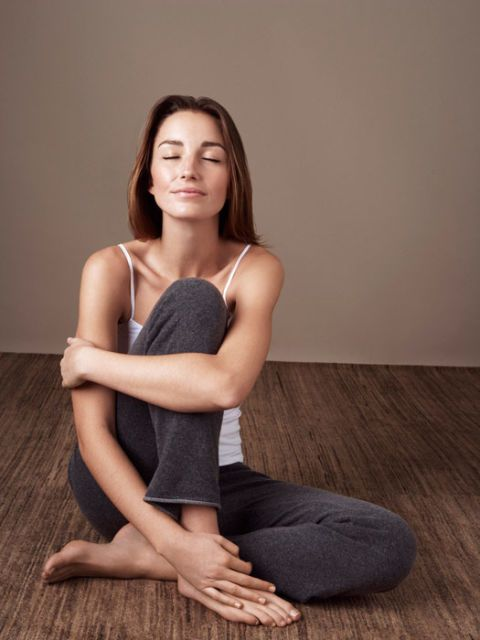 woman in camisole and yoga pants sitting on floor