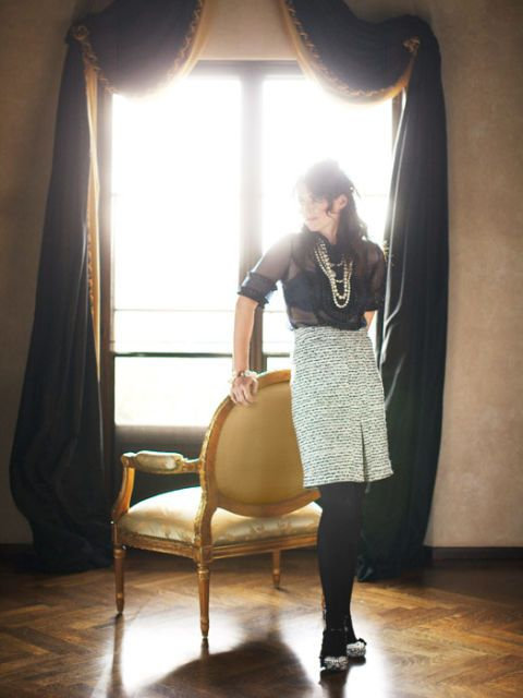 julia ormond in skirt and blouse holding chair in front of lit window