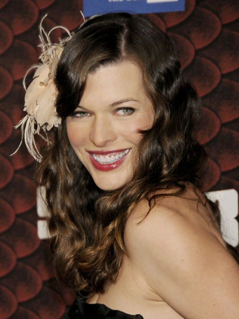 milla jovovich wearing a feather hair accessory
