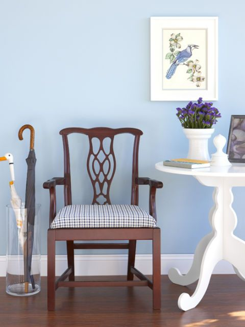 a reupholstered chair in a blue room with table and umbrella stand