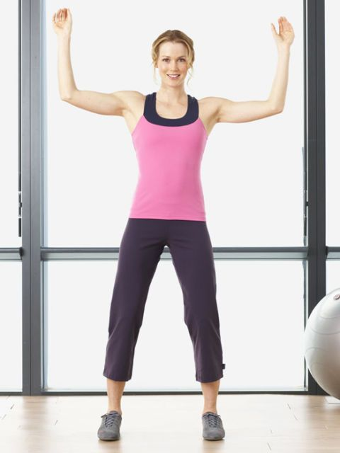 woman in workout clothes in gym with arms over her head