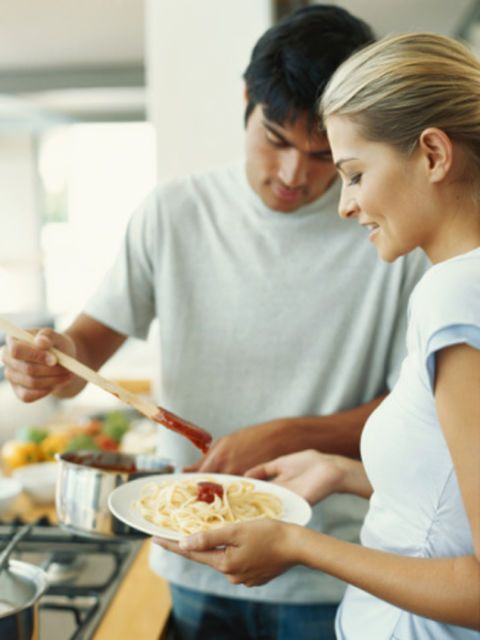 man and woman cooking pasta
