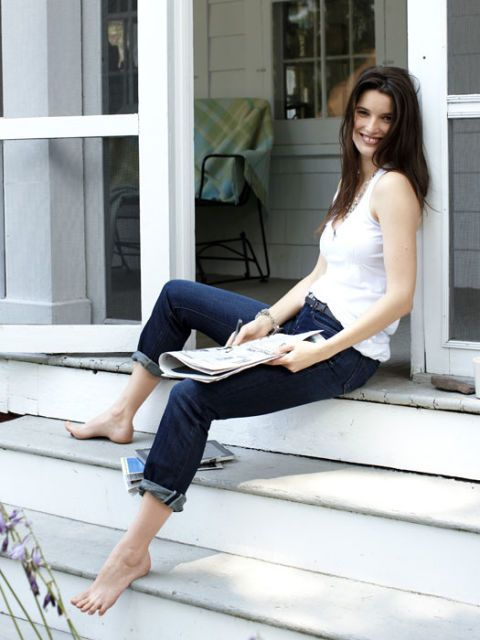 woman wearing jeans sitting on porch