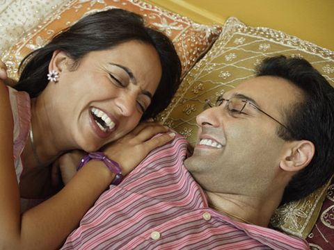 laughing couple laying on pillows