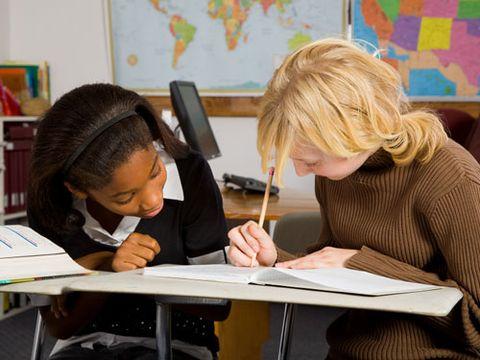 two schoolgirls working together at desks in classroom