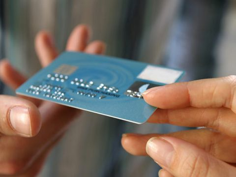 hand giving credit card to another person in a transaction