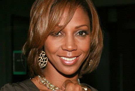 actress and celeb holly robinson peete touching her necklace