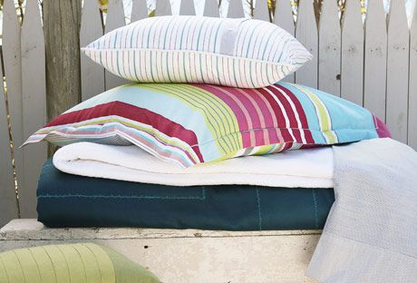 sheets and pillows on bed outside with sand and white picket fence