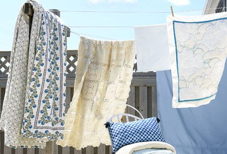 blue and white sheets hanging from a clothesline outside in front of fence