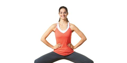 woman on white background doing ballet squat in exercise clothes