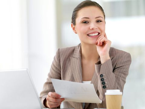 young businesswoman holding paper over a laptop and paper coffee cup