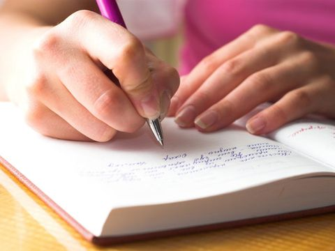 womans hands writing in a diary with pink pen