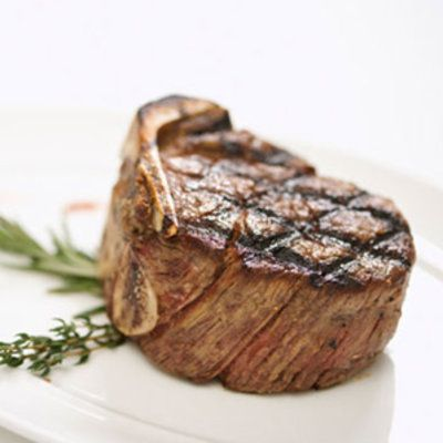 a steak that has been grilled and garnished on a white plate