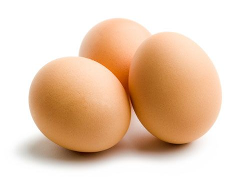 three brown eggs on a white background