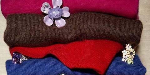 colorful cashmere sweaters folded in pile with cocktail rings