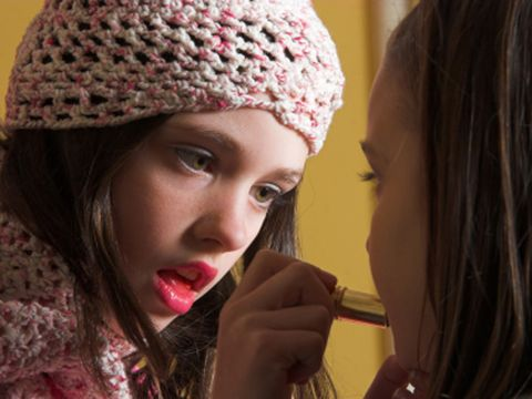 young girl applying lipstick to her friend