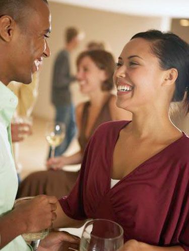 man and woman laughing at cocktail party