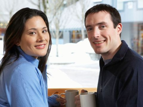 man and woman sitting together with mugs looking at snow