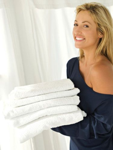 blonde woman in one shoulder shirt carrying stack of folded white towels