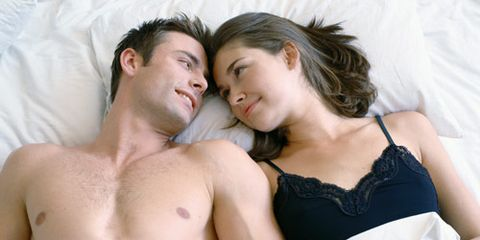 man and woman with heads touching in bed