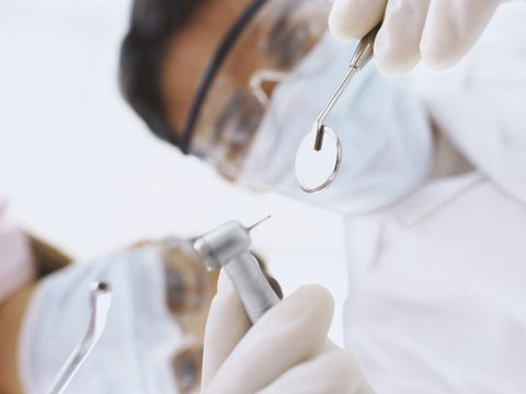 dentists looking at patient with drill and mirror