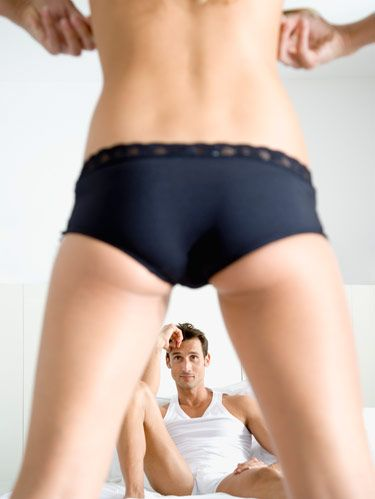 woman in black panties facing man on bed