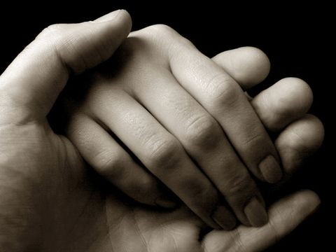black and white photo of two hands holding each other