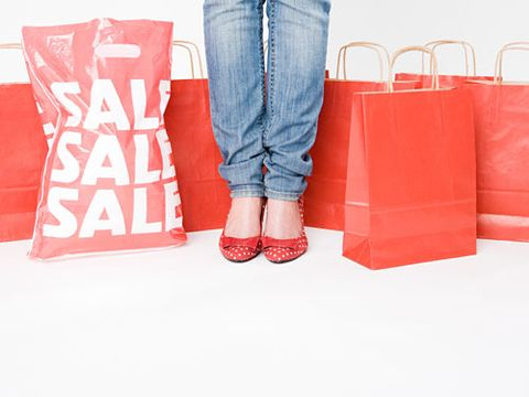 legs of woman standing with red shopping bags