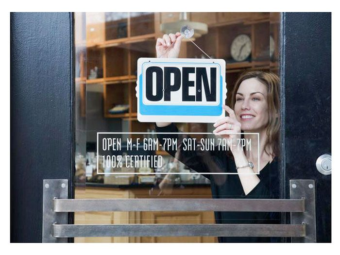 woman hanging sign in window