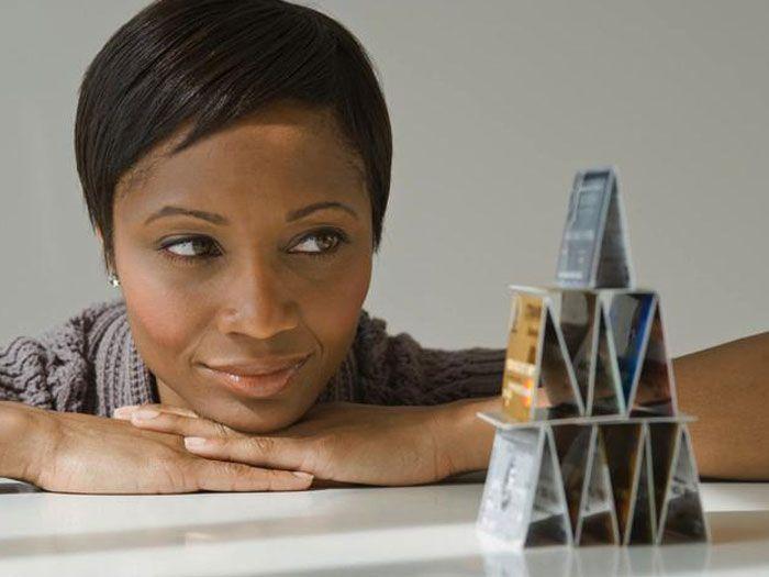 woman looking at pyramid of credit cards
