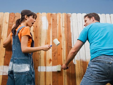 man and woman having a fight while painting a fence