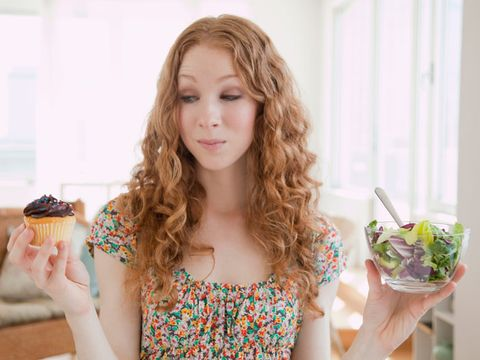 woman holding a cupcake and salad