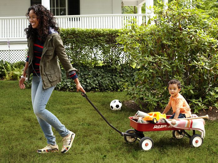 woman in jeans pulling wagon with her son