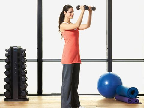 woman lifting dumbbells to do chest fly in gym