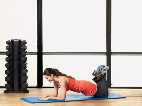 woman in gym on yoga mat in half plank position