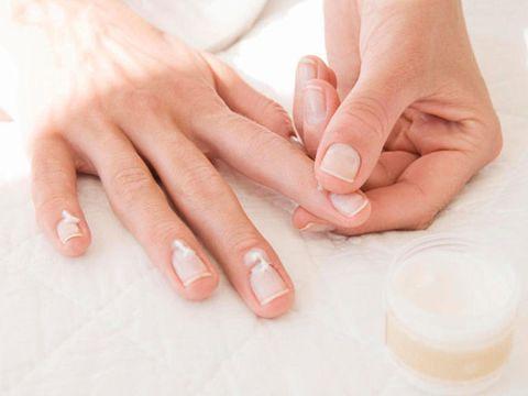 woman rubbing cuticle cream on hands