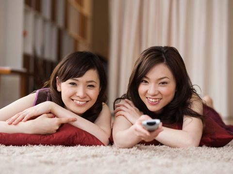 two women on floor watching tv with remote control