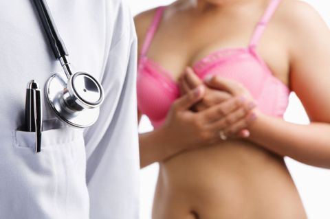 woman clutching breast at doctors office