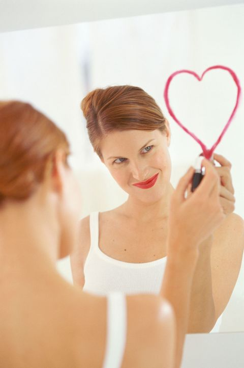 woman drawing a heart on her mirror