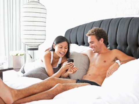 Couple with cell phone on a bed