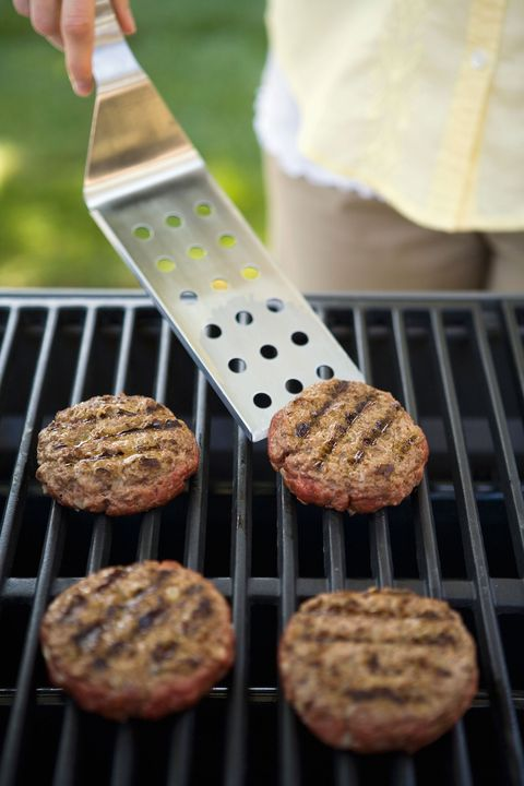 woman flipping burgers on a grill