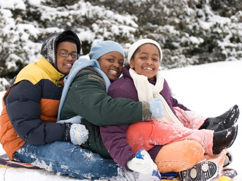 three kids sitting on sled in snow