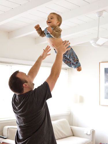man tossing baby into the air