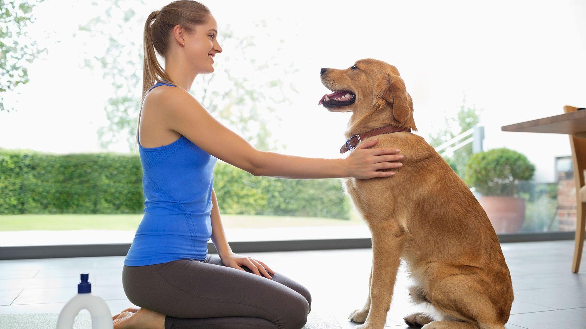 woman in yoga clothing petting dog
