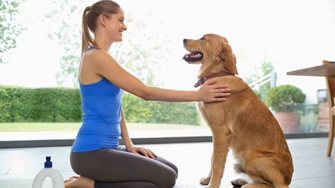 woman in yoga clothing petting dog