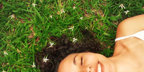 woman lying in grass happy and smiling