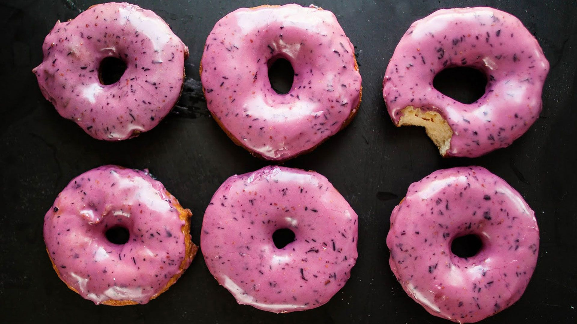 six donuts with pink icing and bite taken out of one
