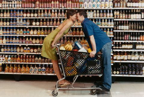 couple canoodling in supermarket over a cart